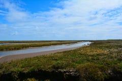 Longue courant/rivière côtière et ciel bleu, point de Blakeney, Norfolk, Royaume-Uni Images libres de droits