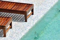 Longue de madera al lado de la piscina Imagenes de archivo