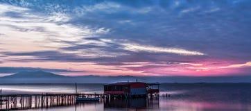 Longue exposition de lever de soleil magique au-dessus de l'océan avec une hutte dans Photos stock