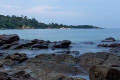 Longue exposition de mer et de roches au-dessus de coucher du soleil Image stock