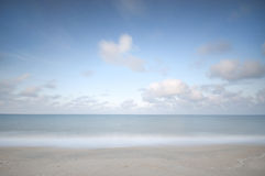 Longue exposition de plage, de vagues, de ciel bleu et de nuages de mouvement Images libres de droits