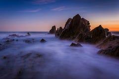 Longue exposition des vagues se brisant sur des roches au coucher du soleil photographie stock