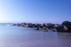 Longue exposition tirée avec des roches sur la mer Image stock