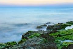 Longue exposition tirée de la mer et des roches avec des algues Image stock