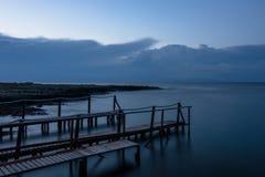 Longue exposition : un pilier en bois après coucher du soleil dans un ciel bleu d'automne Photos stock