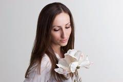 Longue femme de cheveux de Brown avec la fleur de visage et blanche subtile photo libre de droits