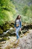 Longue femme de cheveux posant en montagnes Images stock