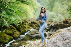 Longue femme de cheveux posant en montagnes Image stock
