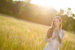 Longue femme rouge de cheveu dans le pré romantique de coucher du soleil Photos stock
