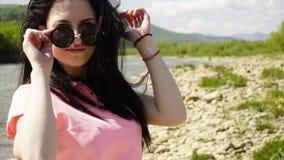 Longue fille de cheveux de brune dans des lunettes de soleil wposing sur le fond de rivière de montagne images stock