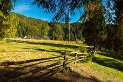 Longue frontière de sécurité en bois le long des prés carpathiens Image stock