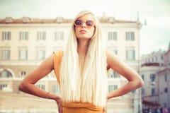 Longue jeune femme élégante de cheveux blonds avec des lunettes de soleil dans la ville photographie stock libre de droits