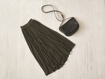 Longue jupe kaki avec le sac à main sur le fond en bois fashionable photographie stock libre de droits