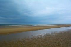 Longue plage sablonneuse de côte de la Norfolk et de bas ciel nuageux bleu-foncé, mer du nord, plage de Holkham, Royaume-Uni Photographie stock libre de droits