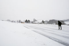 Longue promenade le long de route neigeuse. Photographie stock libre de droits