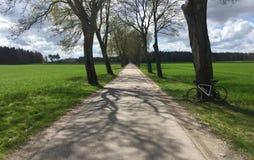 Longue route de campagne pour faire un cycle avec le vélo Images libres de droits