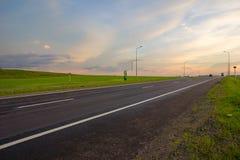 Longue route droite menant dans le coucher du soleil images libres de droits