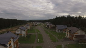Longue rue de vue de village supérieur de cottage contre la forêt banque de vidéos