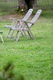 Longues chaises vides dans le jardin Photographie stock