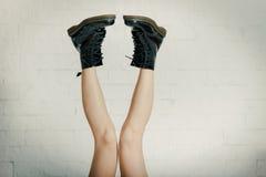 Longues jambes dans de grandes chaussures noires Image stock