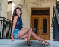 Longues jambes dans la bonneterie sur des escaliers Images stock