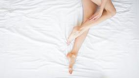 Longues jambes de femme avec la peau molle lisse Fermez-vous de la femelle avec les jambes soyeuses saines parfaites p?lent apr?s photo libre de droits