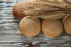 Longues oreilles de blé de pain de pain frais sur la surface en bois Photo libre de droits