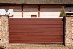 Longues porte en métal et pièce brunes d'une barrière en pierre sur la rue image libre de droits