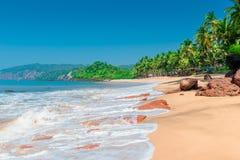 Longues vagues de mousse sur une plage sablonneuse images stock