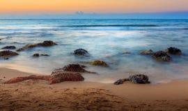 Longues vagues et roches d'exposition sur le coucher du soleil Photos libres de droits