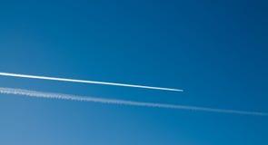 Longues voies d'avion dans le ciel bleu Images stock