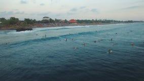 Longueur aérienne des surfers dans l'océan attendant la grande vague dans la soirée banque de vidéos