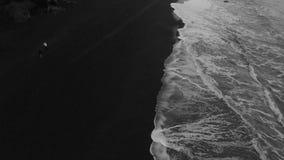 Longueur aérienne des vagues se cassant contre la plage noire de sable en Islande banque de vidéos