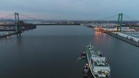 Longueur aérienne du ` s de remorqueur guidant un cargueur dans le port banque de vidéos