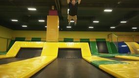 Longueur au ralenti d'un jeune athlète masculin ayant l'amusement sautant sur le trempoline professionnel, faisant des sauts péri banque de vidéos