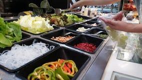 Longueur de légume différent choisi de femme sur la nourriture de approvisionnement de buffet dans le restaurant d'hôtel avec les banque de vidéos