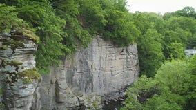 longueur de l'antenne 4K Mouche en canyon Grimpeur sur le mur de roche banque de vidéos