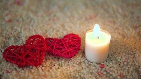 Longueur de la décoration et de la bougie de coeur brûlant sur le sable Jour de Valentine banque de vidéos