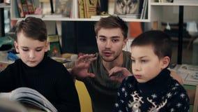 Longueur de mouvement lent du jeune professeur masculin attirant expliquant quelque chose à ses deux petits garçons d'élèves sur  clips vidéos