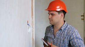 Longueur de mouvement lent du travailleur de la construction ou du constructeur masculin faisant des mesures et notant son calcul banque de vidéos