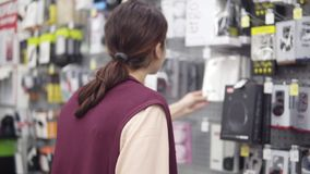 Longueur de postérieur d'une fille de brune prenant une boîte avec des écouteurs d'affichage dans le magasin de l'électronique banque de vidéos