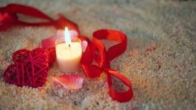 Longueur du Saint Valentin, du ruban et de la bougie de décoration brûlant sur le sable banque de vidéos
