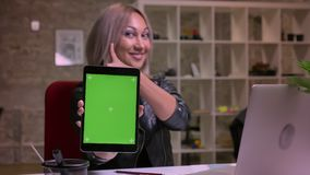 Longueur impressionnante de la fille blonde caucasienne tenant son comprimé avec l'écran vert là-dessus et souriant avec élégance banque de vidéos