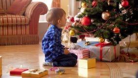 longueur 4k de 3 années de petit garçon s'asseyant sur le plancher au salon et regardant sur l'arbre de Noël décoré banque de vidéos
