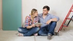 longueur 4k de jeune famille choisissant de nouveaux meubles pour leur nouvelle maison Couples se reposant sur le plancher et à l banque de vidéos