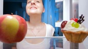 longueur 4k de jeune femme prenant la pomme fraîche du réfrigérateur à la cuisine Concept de nourriture saine et de nutrition banque de vidéos