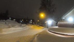 longueur 4K des chutes de neige lourdes dans une rue vide dans une ville avec les réverbères colorés décoratifs clips vidéos