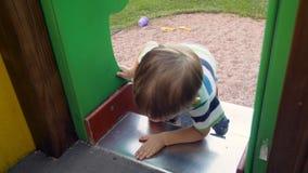 longueur 4k du garçon mignon d'enfant en bas âge essayant de s'élever sur la glissière élevée au terrain de jeu clips vidéos