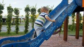 longueur 4k du petit garçon d'enfant en bas âge essayant de s'élever sur la glissière élevée au terrain de jeu clips vidéos