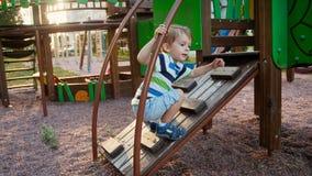 longueur 4k du petit garçon d'enfant en bas âge luttant pour s'élever sur l'échelle en bois au terrain de jeu en parc clips vidéos